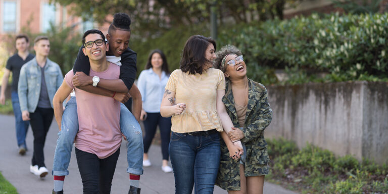 A multi-racial group of university students cheerfully walk down a sidewalk together. One student is carrying his boyfriend on his back.