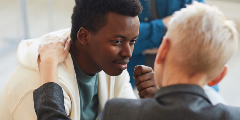 High angle view at young African-American man smiling gratefully to psychologist while while in support group circle